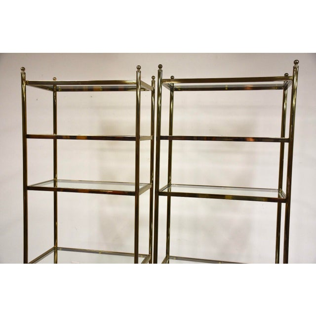 "A pair of modern brass and glass Hollywood Regency style etageres or display cases. 30"" wide. 16.25"" deep. 81.5"" tall."