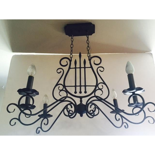 Metal Mediterranean or Spanish-style harp-shape chandelier. This decorative fixture has beautiful scroll detail with a...