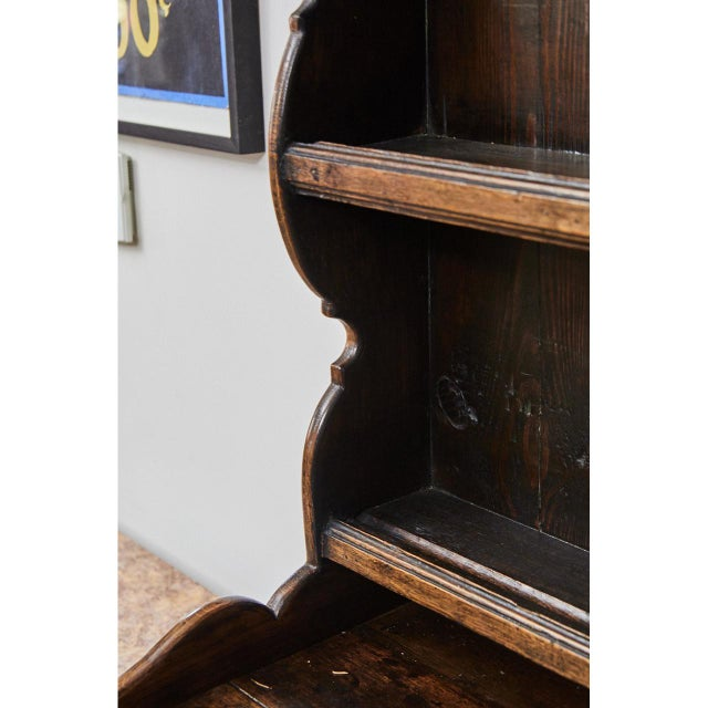 This English oak dresser has an 18th C. base with a 19th C. top. The piece has three shelves over three drawers and two...