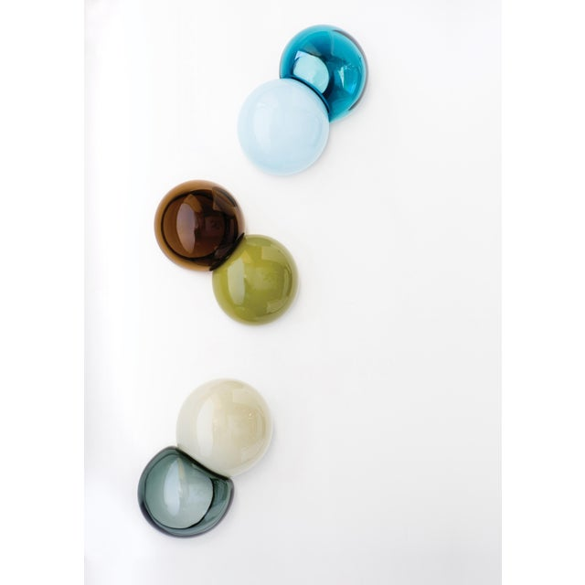 Each SkLO meld wallpiece consists of two complementary colored spheres, each approximately 6″ (15cm) in diameter fused...