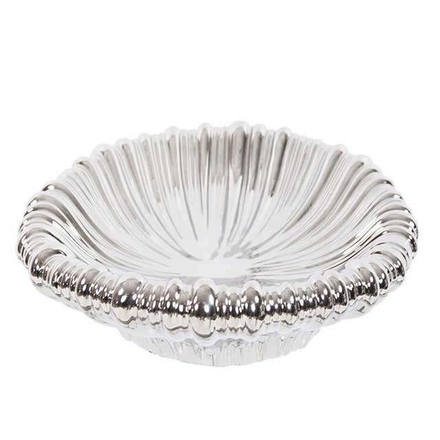 The Metallic Silver Ribbed ceramic tray is striking in every way. It features an oval shape characterized by an organic...