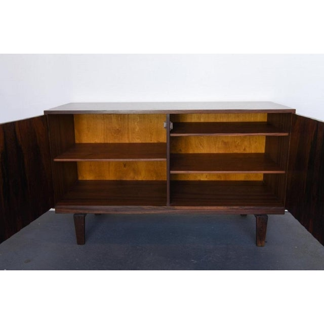 Rosewood with brass hardware. Has three removable shelves. Lovig stamp to the back.