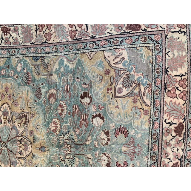 This antique Persian rug, made during the mid-20th Century, has been hand knotted in hues of celadon green, burgundy rose,...