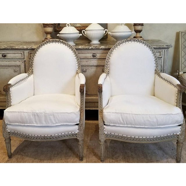 PAIR of 19th C Louis XVI Bergeres with arched top back, generous proportions, painted fine hand carved wood frame. Newly...