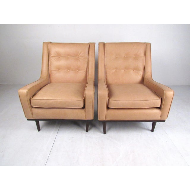 This pair of modern high back lounge chairs features tufted leather upholstery, tapered wooden legs, and comfortable...