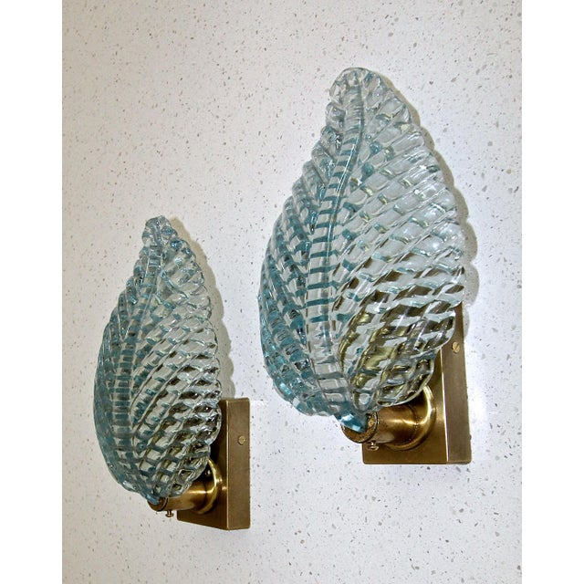 Pair of aqua blue Italian glass leaf shaped wall sconces with brass fittings and backplates by Barovier & Toso. The blue...