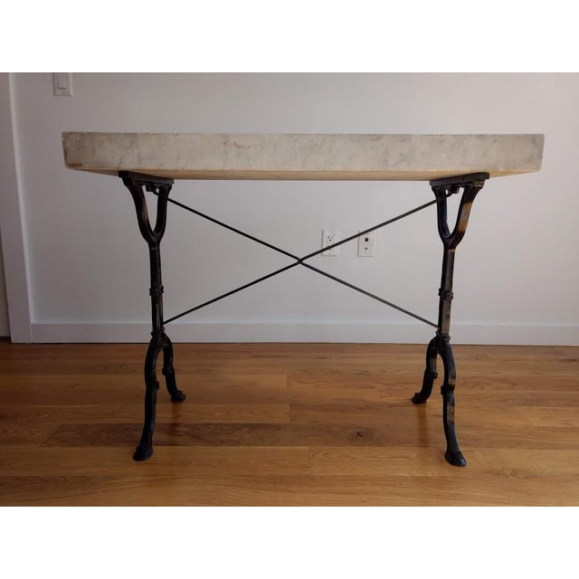This light grey marble table with dark grey veining on a vintage black painted cast iron French bistro base can be used as...