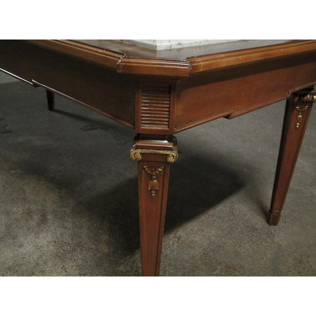 France Circa 1940 A signature Jansen mahogany coffee table with cream marble top. The legs feature low relief gilded...