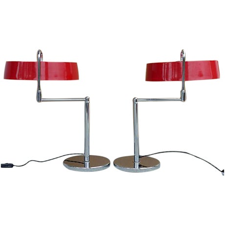 A pair of high-quality vintage Italian lamps featuring a thick solid steel base with polished top and red enameled metal...