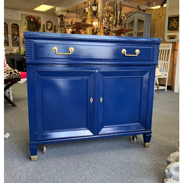 Hollywood regency navy blue lacquered bar cabinet with brass toned hardware and brass feet caps. This is a very finely...