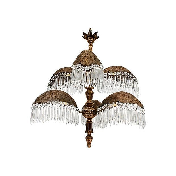 Six-arm palm frond chandelier with hanging glass prisms. The frame is made up of delicate reticulated brass leaves. Wired...