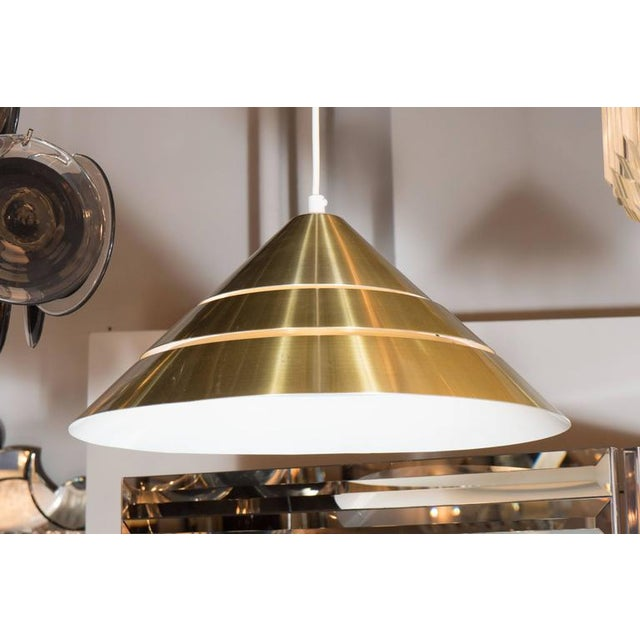 A Mid-Century Modernist segmented brass conical pendant with white enameled interior by Hans-Agne Jakobsson. The overall...