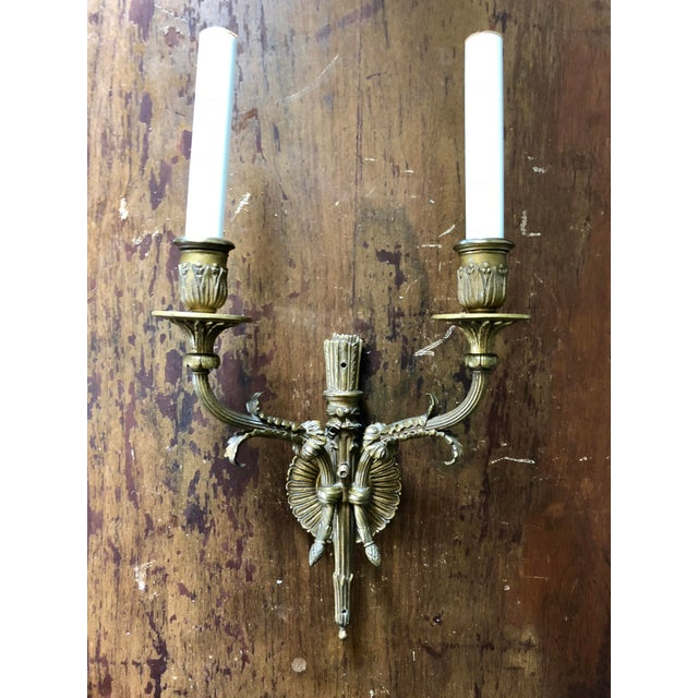 Pair of early 20th century brass two light wall sconces in a quiver and arrows design.
