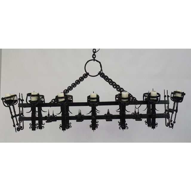 A heavy, iron chandelier in medieval revival and Henry III styles; hand wrought decoration, with honeycomb wax candle...