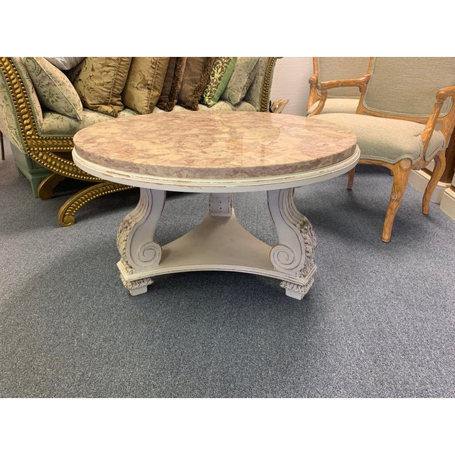 Neoclassical aurora blush beige marble table with antiqued white wash scroll base. Round aurora marble slab sits atop a...