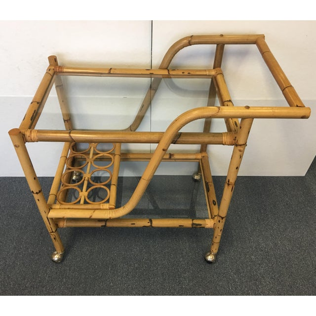 Vintage Bamboo & Rattan Bar Cart. Two tier. Glass Shelves. 8 bottle holder slots. Sits on 4 silver tone ball castors....