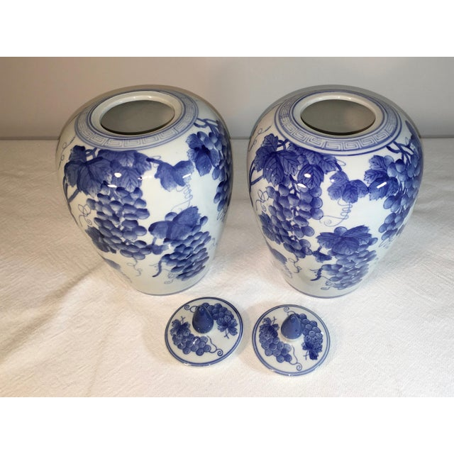 Two vintage ginger jars made in China. These are blue and white transferware with a grapes motif. Some of the design is...