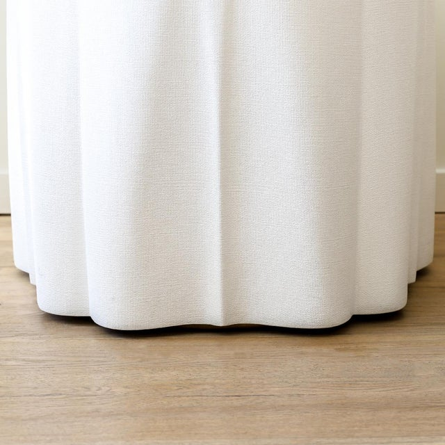 """Round side table in faux jute imitating the cascade of a tablecloth. The dimensions are 25"""" D x 26"""" H and the material is..."""
