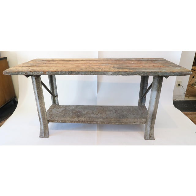 Work table with wood plank top and galvanized metal base with low shelf. Tons of character and age.