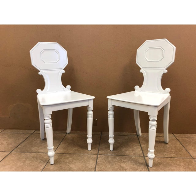 Pair of antique Regency hall chairs. The chairs are mahogany with a white lacquered finish.