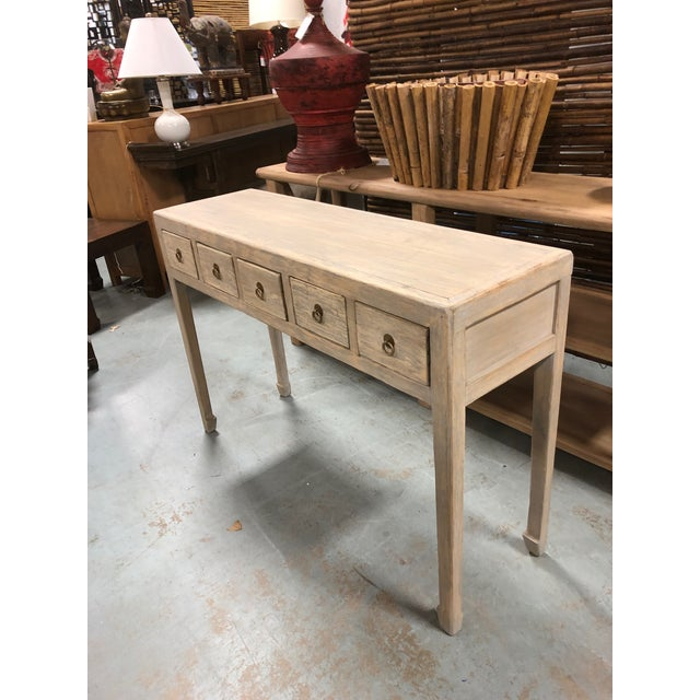 Asian style console table with a gray washed finish, five drawers, and antique brass ring hardware. This is console is...