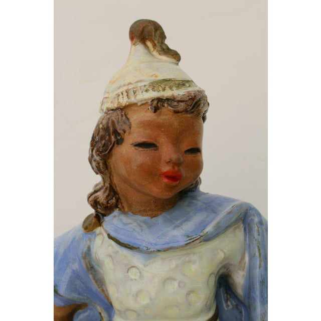 A wonderful Austrian Secessionist glazed terra cotta figure, which is monogrammed on the base and incised Wien for Vienna....