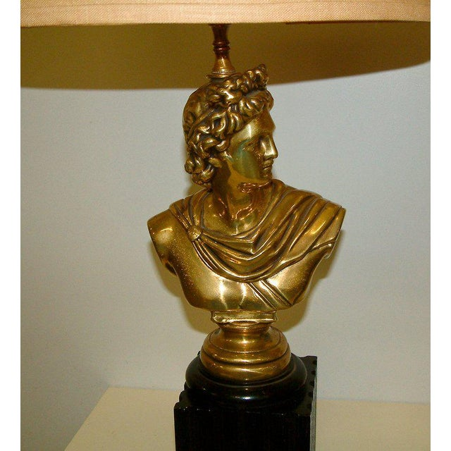 United States Circa 1950 A stylized pair of brass clad lamps in the classical tradition. The lamps have fluted enameled...