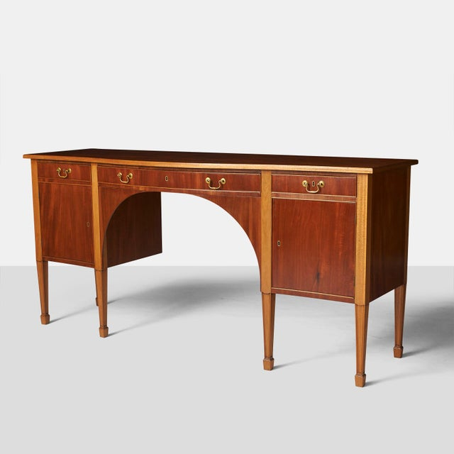 A mahogany Sheraton style sideboard, lightly curved front with three drawers and two doors behind which there are shelves....