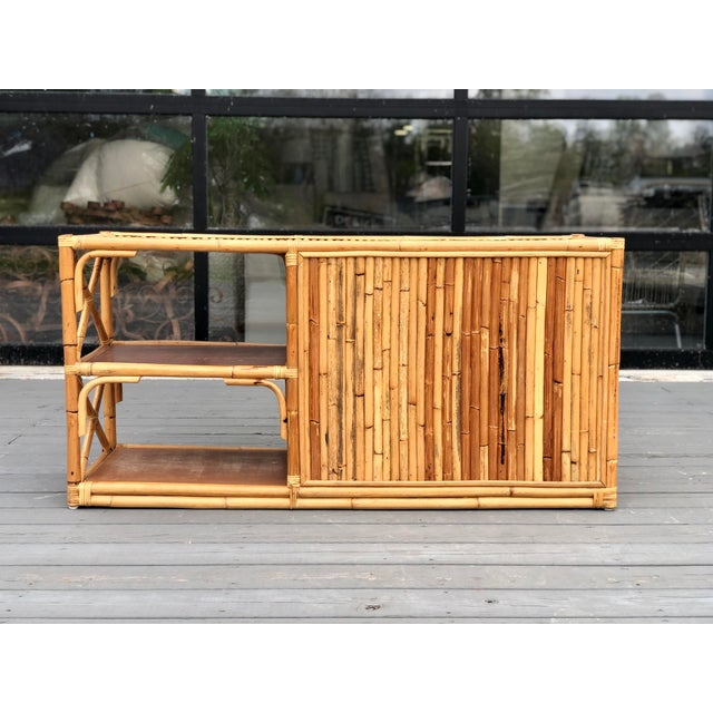 Beautiful vintage rattan buffet/credenza/bar with unique round rattan pulls. Two cabinet doors with functional shelving as...