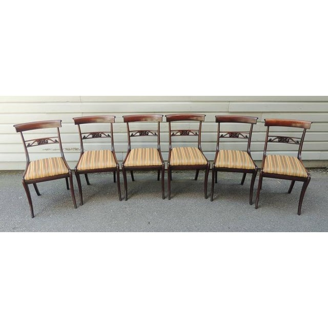 This set of six dining chairs were made in England in the early half of the 19th century, circa 1820, by noted furniture...