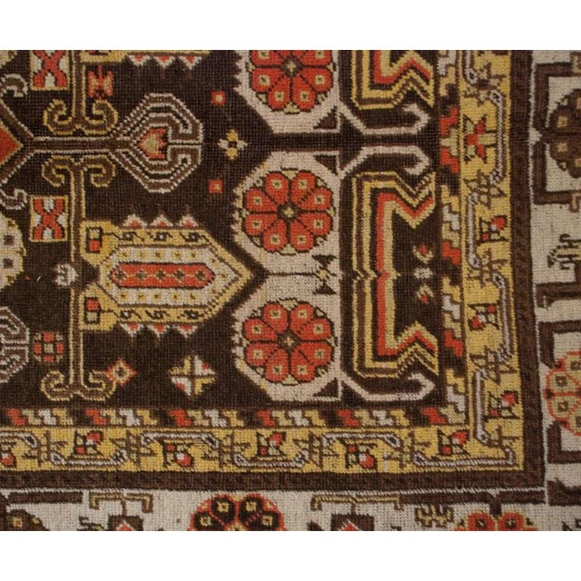 An early 20th century Central Asian Khotan rug with asymmetrical geometric and floral pattern surrounded by a contrasting...