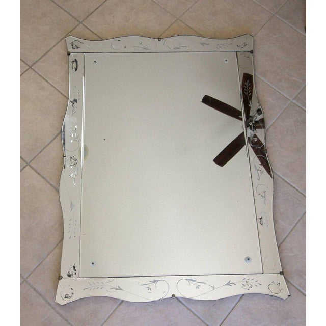 Rectangular Art Deco scalloped or wavy edge wall mirror with nicely etched mirrored panels and inset rosettes. Mirror has...