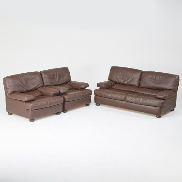 Roche Bobois leather sofa and a pair of lounge chairs with enameled wood feet, France, circa 1980 - a set. Stamp found on...