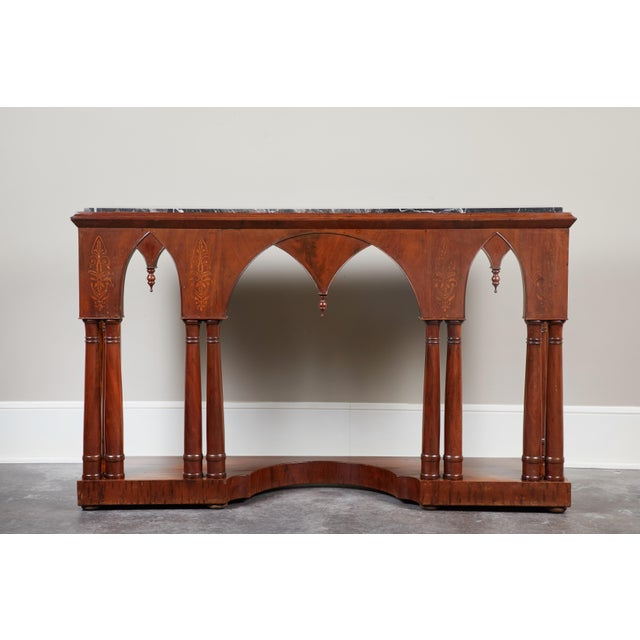 A gothic style French Charles X mahogany console, circa 1840. Black marble top, with bottom featuring a platform base with...