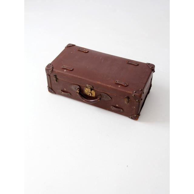 A vintage leather suitcase circa 1930. The dark brown luggage case features enforced corners, a leather handle and loops...