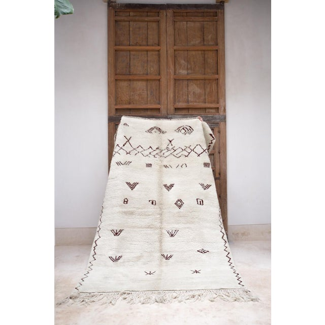 Beautiful in its simplicity and open space. Contemporary natural white wool area rug with brown Berber symbols handmade in...