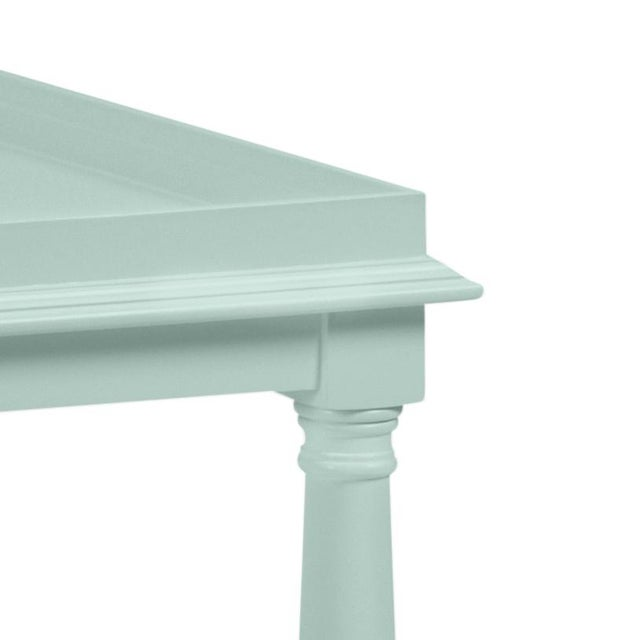 Made of acacia wood, this cocktail table features a gallery shelf and turned legs. Finish is Benjamin Moore Palladian Blue.