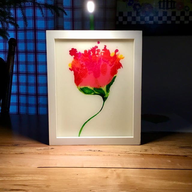 Poured resin botanicals left to dry then encapsulated in 100 percent clear resin. Then framed . When lite well they look...