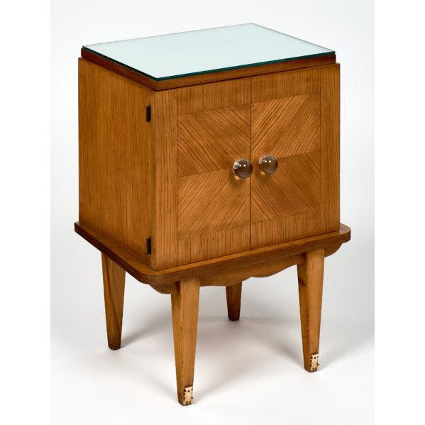 A pair of French mid-century modern side tables, each featuring two doors with clear Murano glass knobs and a single shelf...