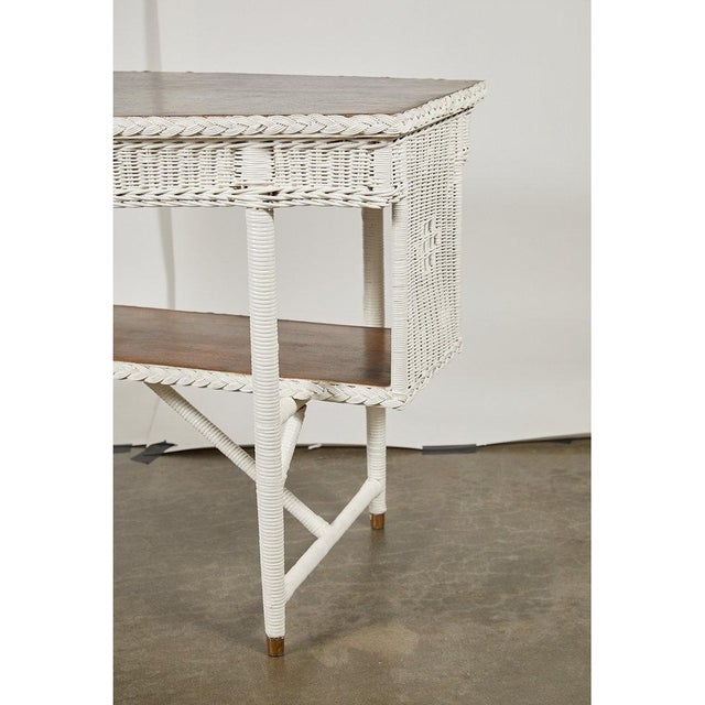 This beautiful wicker table from the 1920's has an unusual shaped oak top and shelf and has been painted with Farrow &...