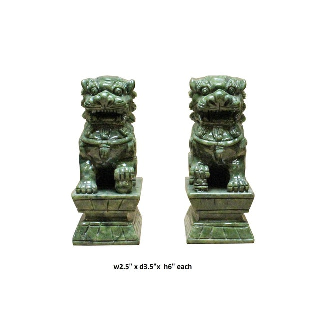 This pair of foo dog figures is made of green color stone, they sit high on a stone base that representing looking far and...