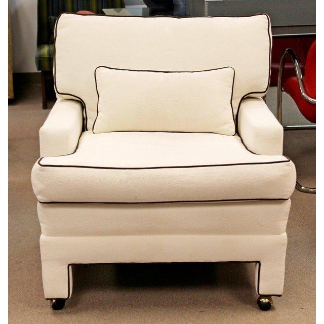 For your consideration is a massive, plush armchair, in a white fabric, with brown trim and brass casters, attributed to...