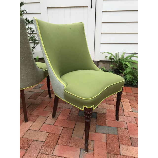 A pair of vintage dining chairs, upholstered in an apple green cotton on the front and a silver blue-green linen bouclé on...