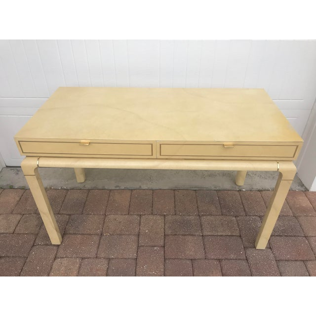 Vintage faux Goatskin or parchment finish desk with brass detailing. Desk has two drawers in front for storage and is...