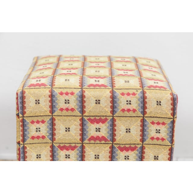 Yellow, blue, ivory and red needlepoint used as upholstery on small footstool.