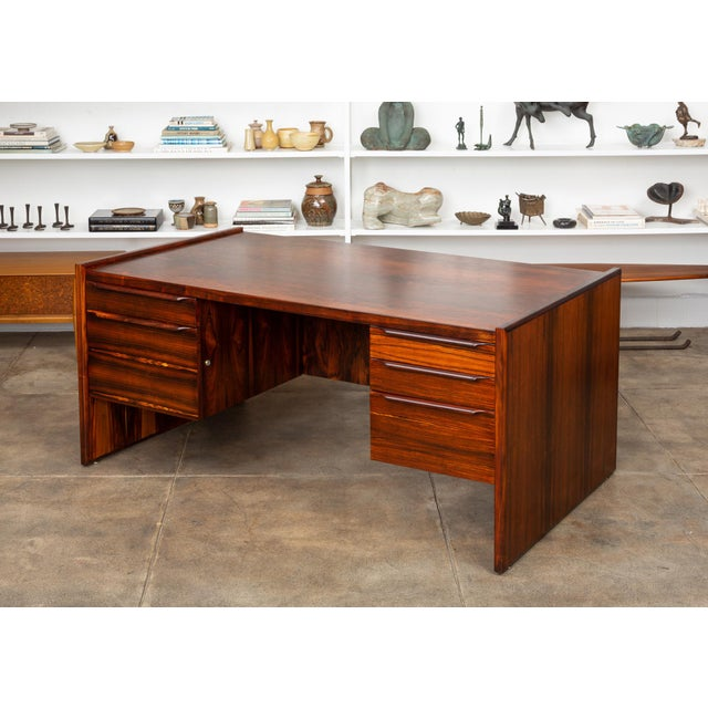 A stunning rosewood executive desk, American, c.1960s. The desk features a highly figured rosewood frame and top with...