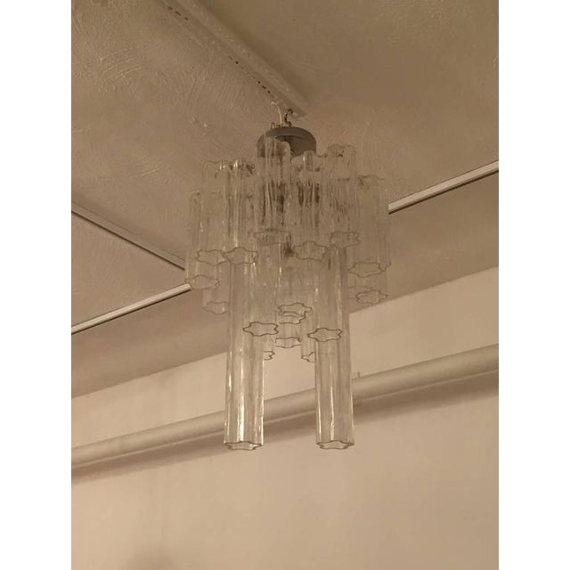 Mid-Century Modern Italian round tronchi chandelier. The glass tronchi tubes hang from hooks onto a nickel frame, as...