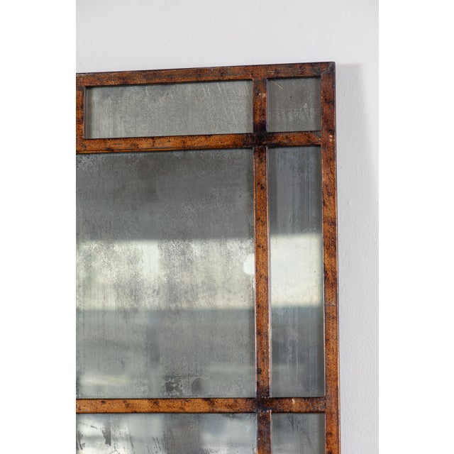 Aged brass frame with antiqued smoked glass mirror. Circa mid 20th century.