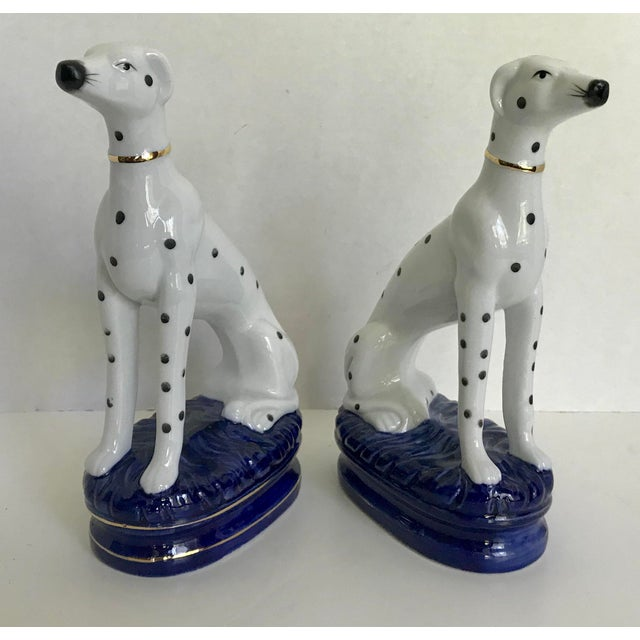 This is a charming pair of porcelain dogs (dalmatians?) sitting upright on indigo blue pedestals. Each dog has a gold...