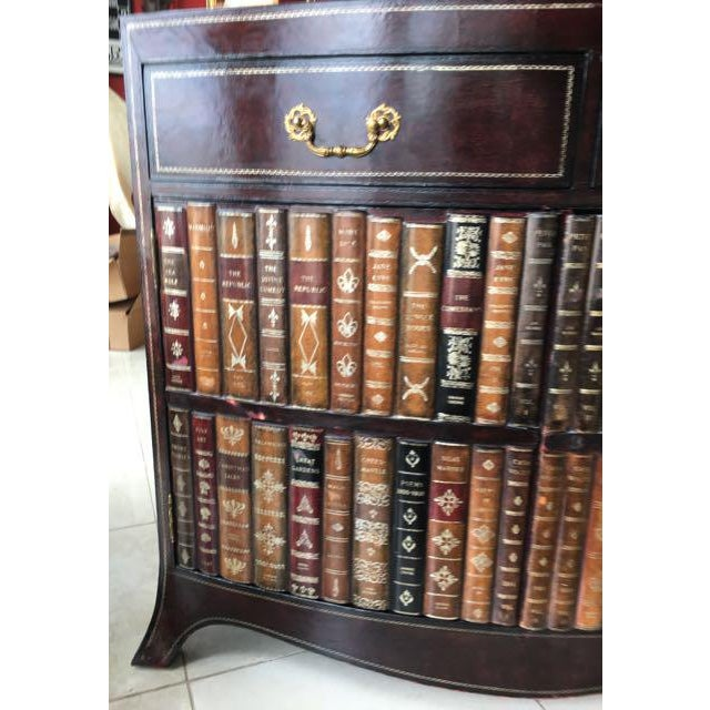 Maitland-Smith faux bookcase cabinet covered with tooled leather. The doors on this bow front cabinet are made to look...